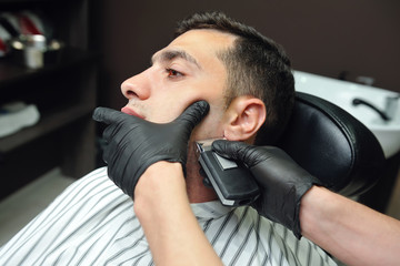 A man in a male barber shop shaves his beard with a trimmer