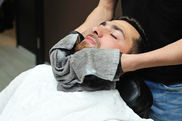 Barber preparing man face for shaving with hot towel on face in barber shop
