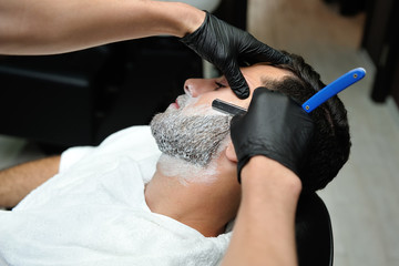 Hairdresser shaves man's beard with a blade in a male barber shop