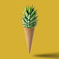 Ice cream cone with pineapple leaves on bright yellow background. Fruit and candy concept.