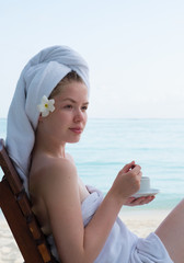 Luxury Maldives spa relaxation. Clean and beautiful girl with towel on head drinking tea near Maldivian ocean. Girl relaxing after spa. Spa at luxury resort vacation time. Beauty and healthcare.