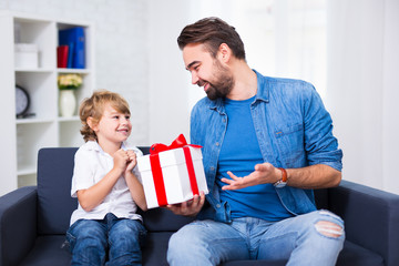 father's day or christmas concept - little son and his father with gift