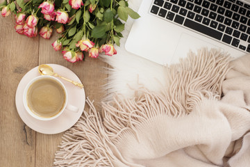 Feminine workplace concept. Freelance workspace with laptop, flowers roses. Blogger working.
