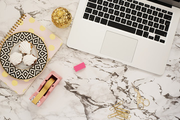 Feminine workplace concept. Freelance workspace in flat lay style with laptop, sweets, golden pineapple, notebook and paper clips on white marble background. Top view, bright, pink and gold