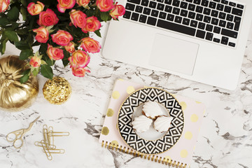 Feminine workplace concept. Freelance workspace in flat lay style with laptop, flowers, golden pineapple, notebook and paper clips on white marble background. Top view, bright, pink and gold