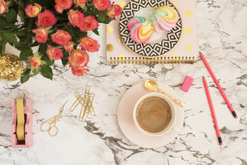 Feminine workplace concept. Freelance workspace in flat lay style with coffee, flowers, golden pineapple, notebook and paper clips on white marble background. Top view, bright, pink and gold