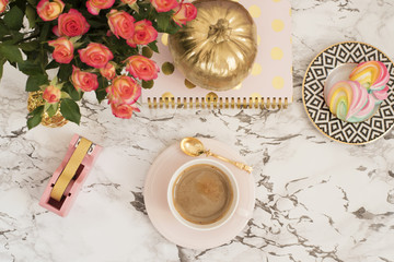 Feminine workplace concept. Freelance workspace in flat lay style with coffee, flowers, golden pumpkin, notebook and paper clips on white marble background. Top view, bright, pink and gold