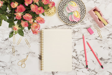 Feminine workplace concept. Freelance fashion comfortable femininity workspace in flat lay style with flowers, golden pineapple, notebook on white marble background. Top view, bright, pink and gold