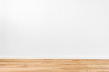 White painted stucco wall and natural wooden ash-tree 3-band parquet board hardwood floor. Flooring...