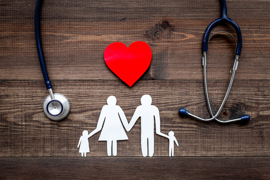 Take out health insurance for family. Stethoscope, paper heart and silhouette of family on wooden background top view