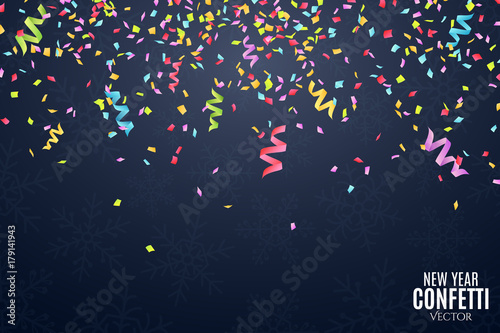 many falling multicolored confetti and ribbons on a dark blue background celebratory background on birthday