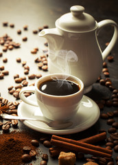 Black coffee in a cup on the table in a composition with coffee accessories on an old background