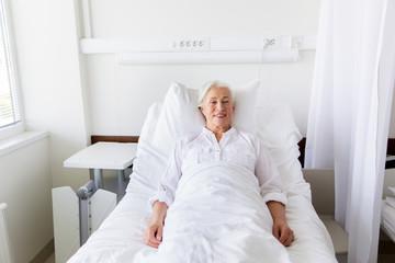 smiling senior woman lying on bed at hospital ward