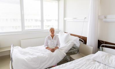 sad senior woman sitting on bed at hospital ward