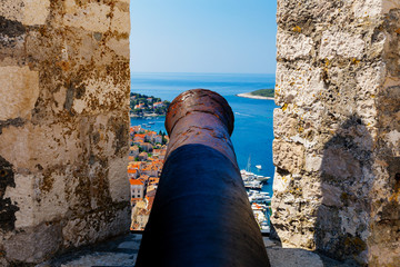 Cannon on the fortress known as Fortica with aerial view of harbor on island Hvar, Croatia