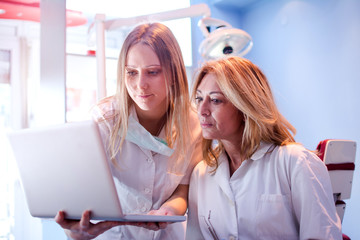 Young student of dentistry or nurse and female dentist looking at laptop together in dental office.