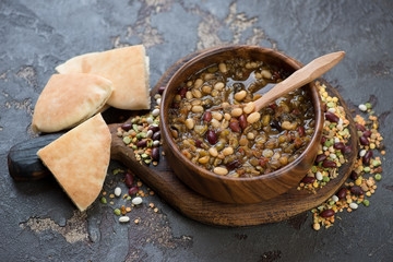 Thick mexican soup with variety of beans and pita, brown stone background, studio shot