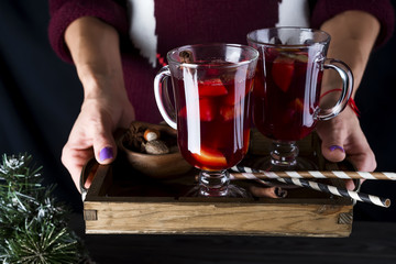 in female hands tray with hot mulled wine