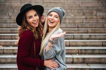 Portrait of two cheerful attractive girls hugging
