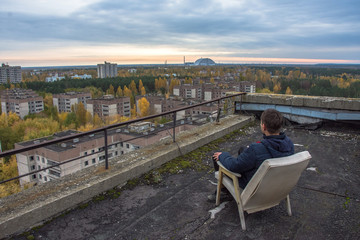 Men on the top of the roof at abandoned Pripyat city in Chernobyl Exclusion Zone at autumn time