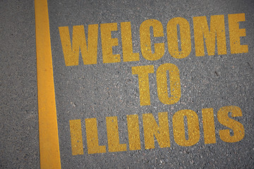 asphalt road with text welcome to illinois near yellow line.
