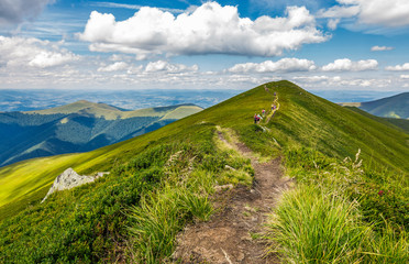 group of tourist hiking the mountains. trail through mountain ridge with grassy slopes leads to its peak. gorgeous summer landscape under the breathtaking cloudscape. conquering altitude concept