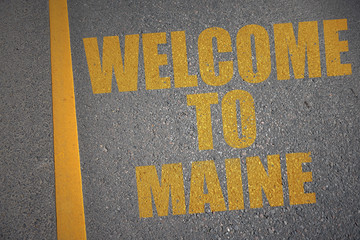 asphalt road with text welcome to maine near yellow line.