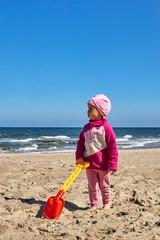 Dziewczynka bawi się na plaży łopatką do piasku.
