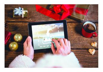 Santa Using a Tablet at Wooden Table Mockup 1