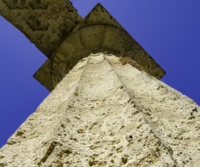 view from the bottom of a column of a Greek temple in the archaeological park of Paestum, Salerno - Italy