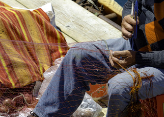 Fisherman repairing a huge fishing net