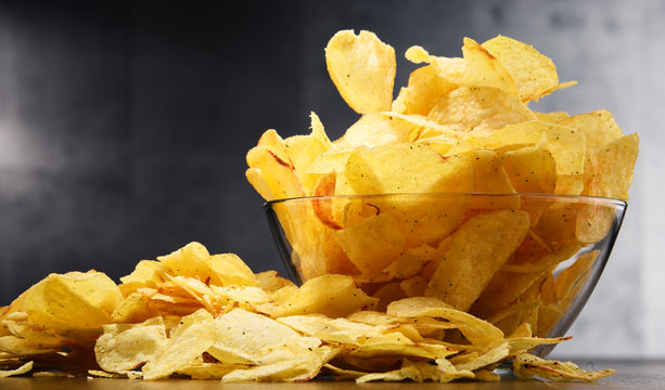 Composition with bowl of potato chips on wooden table