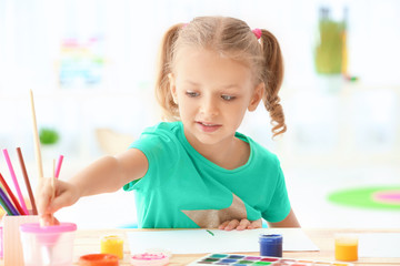 Cute girl painting picture at table indoors