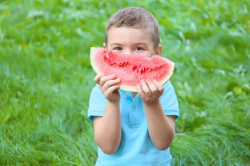 Cute boy eating watermelon, outdoors
