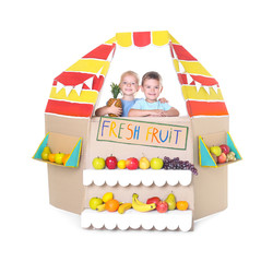 Little children playing with cardboard stall on white background