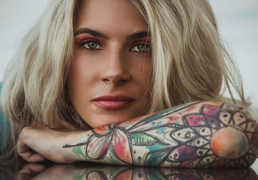 Closeup portrait of. Beautiful girl put her head in her arms with tattoos. expectation.