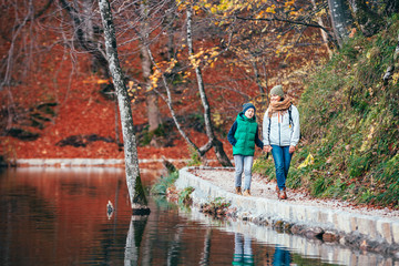 Mother and son walk in beautiful autumn park near lake
