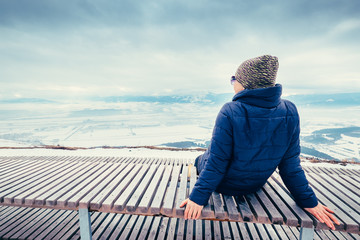 Woman relax on top hill point with beautiful panorame view on winter city