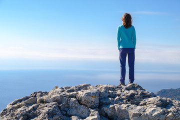 Athletic young woman standing on the rocky top of the mountain against the blue of sky and sea. Back to the camera