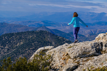 Athletic young woman walking on the rocky top of the mountain on the background of blue sky