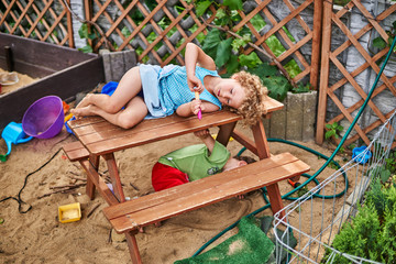 Mała dziewczynka leży na ławce na placu zabaw dla dzieci.