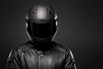 Man wearing a black leather motorcycle jacket and helmet on dark background.