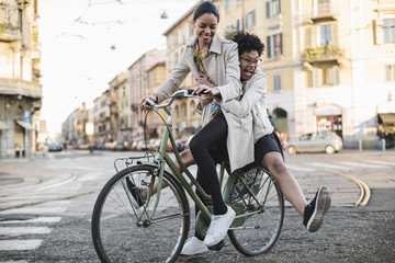 Two young female friends on the bicycle in the city