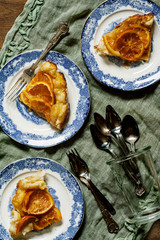 Orange tarte tatin and cutlery on table cloth. Seen from above.