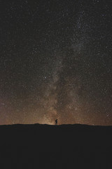 Small silhouette of man under sky of stars