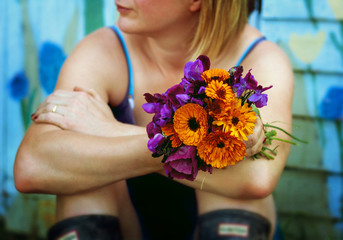 A woman in summer clothing and wellies holding a bunch of flowers