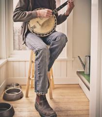 man on yellow stool playing vintage banjo