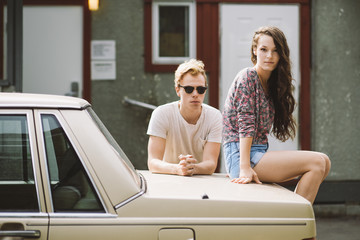 A rebellious pair of teenagers relaxing on a car looking into the camera