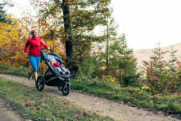Running mother with stroller enjoying motherhood at autumn sunset