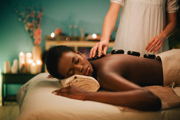 Woman receiving hot stone massage at luxury spa